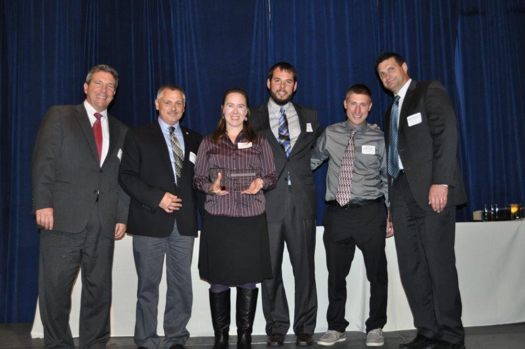 Pictured left-right: DCA President and Wohlsen Senior VP Mike Berardi, Chief Estimator Mark Benson, Kalmar Nyckel Captain Sharon Dounce, Project Manager Brandon Cale, Foreman Kevin Woodland, and Deputy Director of the Office of Management & Budget for Delaware Brian Maxwell accepting the Delaware Contractors Association Excellence in Construction award for the Kalmar Nyckel project.